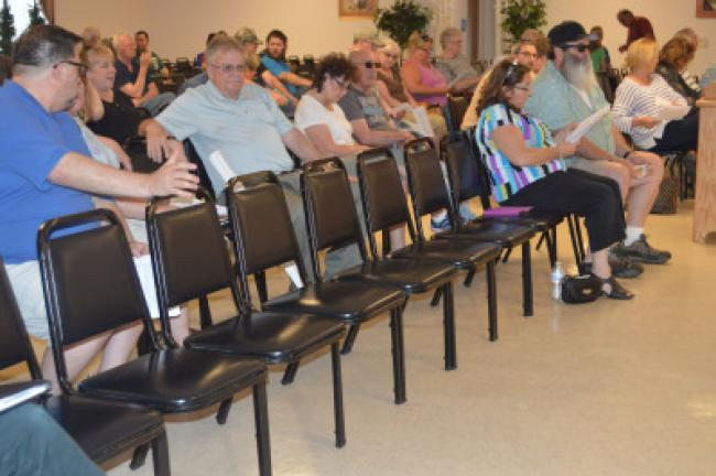 Chairs normally reserved for Atlantic Wind employees and attorneys remained empty at the final zoning hearing board meeting to decide its application to build up to 37 wind turbines in Penn Forest Township. JUDY DOLGOS-KRAMER/TIMES NEWS