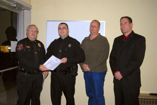 RON GOWER/TIMES NEWS Lansford part-time police officer Tom Fort, second from left, receives letter of commedation from Chief of Police John Turkmanovich, left, during meeting of Lansford Borough Council last night. Looking on are Ron Hood, second…