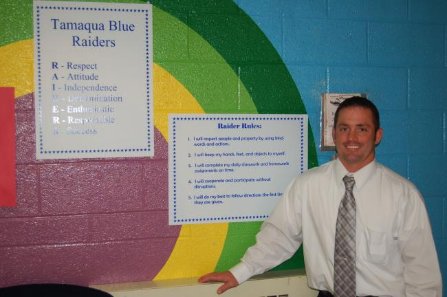 JOE PLASKO/TIMES NEWS Tamaqua Area Assistant Elementary Principal James J. Fasnacht displays signs for the Raider Rules code of conduct implemented in the school district's three elementary schools this year.