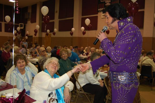 Gail Maholick/TIMES NEWS Virginia Horner of Mahoning Valley swoons as Elvis Impersonator Brad Crum sings to her during the Lehighton Senior Center's 35th anniversary celebration.