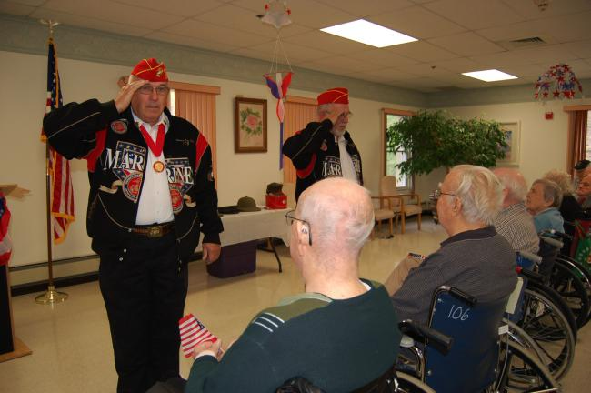 Gail Maholick/TIMES NEWS George Unangst, left; and Nick Hawkey, right; salute veterans World War II veterans Luther Minnich and David Hegarty.