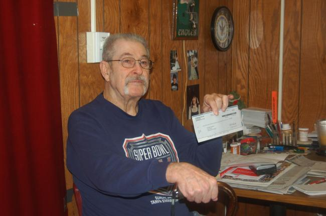 "CHRIS PARKER/TIMES NEWS Navy veteran Richard McGinley, 73, of Lehighton, holds the ""sweepstakes"" check he received in the mail."