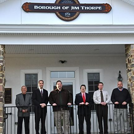 VICTOR IZZO/SPECIAL TO THE TIMES NEWS Standing beneath the new Borough of Jim Thorpe sign on the front of the new office building and police station are, from left, Mayor Ronald Confer, Councilman Jeremy Melber, council President John McGuire,…