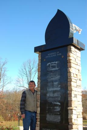 Donald Christ, the first park director, stands at the reverse side of an eternal flame, which shows scenes of local memories. It is in the Gateway area.