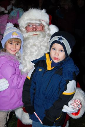 Kate Halenar, left, 4, and Ronnie Snyder, 5, both of Lehighton, get a hug from Santa during his visit to Lehighton Park Amphitheater on Friday.