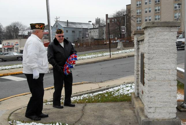 RON GOWER/TIMES NEWS Frank Bayer, right, president of the World War II Last Man's Club in Lehighton, hands a wreath to Glenn Troutman of the Lehighton United Veterans Organization, during a Pearl Harbor remembrance program, yesterday, in Lehighton…