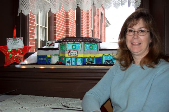 Sheryl Beltz, Barnesville, started a tradition five years ago by establishing a gingerbread house contest to benefit the U. S. Marine Corps League's Toys for Tots program. Here, Beltz poses with one of this year's entries, a model of Thorn's Cycle…