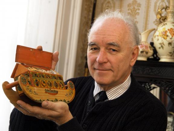 AL ZAGOFSKY/SPECIAL TO THE TIMES NEWS John Gunsser holds a late 19th century Noah's Arc toy. The toy, an inexpensive German assemblage of wood covered with a lithographed design, served to illustrate a Biblical lesson.