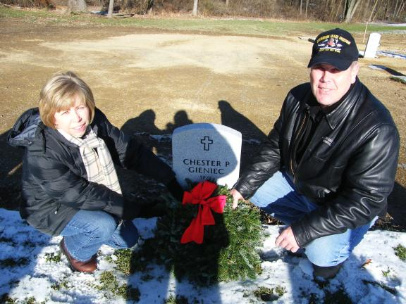 "CAROL ZICKLER/SPECIAL TO THE TIMES NEWS Kathy and Brian Sommers place a wreath on the grave of Chester ""Ace"" Gieniec of Summit Hill at Indiantown Gap National Cemetery. Kathy serves as VFW auxiliary president and her husband serves as commander of…"