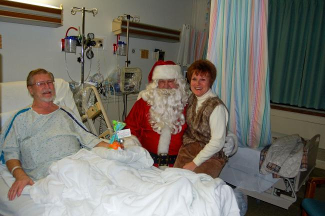 TERRY AHNER/TIMES NEWS Patient Herman Silfies is all smiles as his daughter, Debbie Siekonic, sits on the lap of Santa Claus during his visit to Palmerton Hospital on Tuesday.
