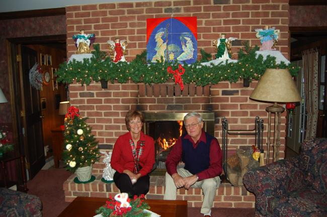 Darlene and Richard (Dick) Nothstein enjoy a moment of warmth in front of their living room fireplace amid their lovely collection of angels.
