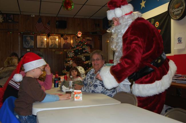 Two Santas meet across the table as Skylar Green dons his hat.