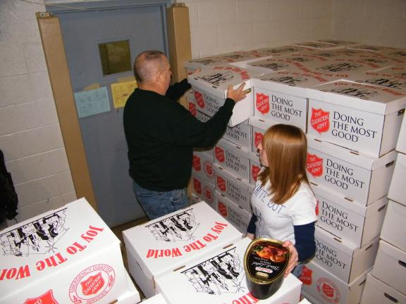 ANDREW LEIBENGUTH/SPECIAL TO THE TIMES NEWS Tamaqua Police Chief George Woodward, left, and Tamaqua Marketing Class volunteer Shauna Bannan help distribute Tamaqua Salvation Army food boxes and hams during the Tamaqua Salvation Army distribution.