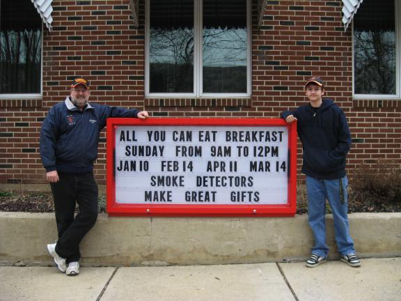 STACEY SOLT/SPECIAL TO THE TIMES NEWS Kyle Behler, right, stands next to the sign he recently installed at the West End Fire Co. No. 2 in Palmerton to complete the rank of Eagle Scout. With him is his father, Dennis Behler of Palmerton.
