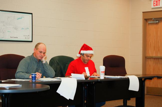 CHRIS PARKER/TIMES NEWS Rush Township supervisors Shawn Gilbert and William J. Sanchez Jr. played Santa for property owners Tuesday by adopting a 2010 budget that keeps the real estate tax the same as this year. That's Sanchez in the Santa cap.