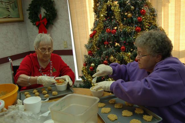 Beulah Melbar and Phyllis Zellers, residents at The Summit at Blue Mountain Health System in Lehighton, enjoy placing homemade Christmas cookies on baking sheets during the annual cookie baking day, held recently at the nursing home.