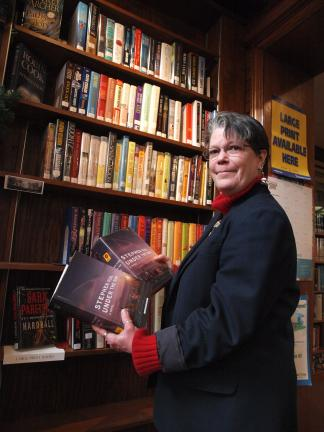 "AL ZAGOFSKY/SPECIAL TO THE TIMES NEWS Standing in front of the new large-print section of the Dimmick Library in Jim Thorpe, director Susan Sterling holds copies of Stephen King's ""Under the Dome"" in both standard and large-print versions. Although…"