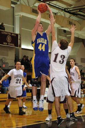 STEVE SHINKO/special to the times news Marian's Drew Sherkness (44) goes over Lehighton's JT Keer with a shot.