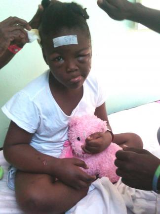 DR PAUL VANEK/ SPECIAL TO THE TIMES NEWS A young Haitian girl with head injuries holds on to her little pink Teddy bear as she awaits surgery at a hospital in Port-au-Prince.