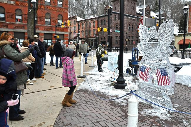 VICTOR IZZO/SPECIAL TO THE TIMES NEWS Drawing crowds of curious visitors to Jim Thorpe's Winterfest 2010, ice sculptor Neil Trimper of Sculpted Ice Works carved large blocks of crystal clear ice into works of art such as the nearby Patriotic Eagle…