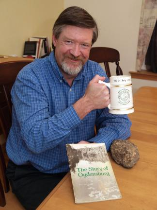 "Matthew Schwartz poses with an Ogdensburg mug, along with a copy of ""The Story of Ogdensburg"", and a zinc ore rock from Ogdensburg, the town where he grew up which was the home of the Sterling Mine of the New Jersey Zinc Company. Strangely,…"