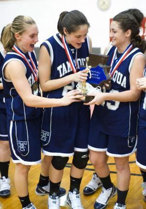 bob ford/times news Tamaqua players, from left, Allison Updike, Amy Zehner and Elissa Streisel hold the Schuylkill League championship trophy after defeating Tri-Valley on Friday night.
