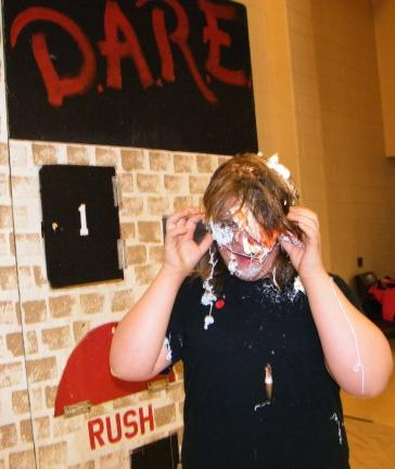 "ANDREW LEIBENGUTH/SPECIAL TO THE TIMES NEWS Rayona Flunara, 11, laughs and tries to see through her eye goggles after receiving an egg pie and silly string ambush when she opened door number nine on the ""Wall of DARE."""