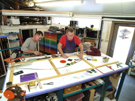 Glass artist Nic East (right) lays out a design across three adjacent windows that will go in the Jewelry Room of his Hill Home Forge B&B as assistant Garry Palumbo prepares foil wrapped glass pieces for the design.