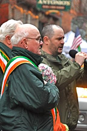 VICTOR IZZO/SPECIAL TO THE TIMES NEWS With Parade Grand Marshall Hugh Dugan in the foreground, AOH member Darren Behan sings the Irish national anthem in both Gaelic and English before the start of the parade.