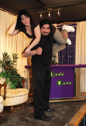"Mark ""Bad Billy Walker"" Davalos holds wife Renee ""Texas Rose"" in a combination wrestling/burlesque move. They are on a stage in their studio where they participated in two episodes of the Jerry Springer Show."