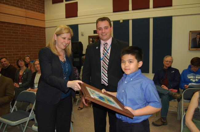 "LINDA KOEHLER/TIMES NEWS Penny Derr, PVE Principal, left, and Joshua Krebs, PVE Assistant Principal, center, presented a framed copy of the winning picture in the ""Design the School Logo Contest"" by the Curriculum Committee of the Pleasant Valley…"