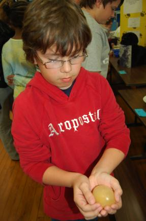 LINDA KOEHLER/TIMES NEWS Nathan Goodhile, a fifth grader at S. S. Palmer Elementary School, shows everyone at the 2010 Palmer/Parkside Science Fair, what an egg looks like after soaking in vinegar and the shell dissolves.
