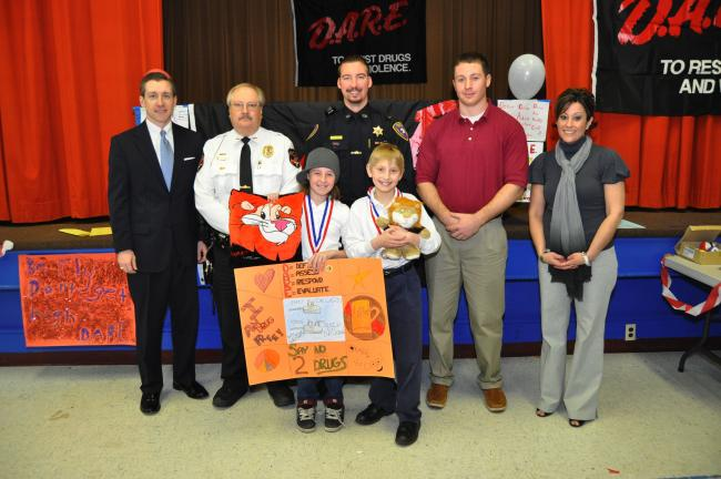 AMY ZUBEK/TIMES NEWS D.A.R.E. graduates Molly Behan and Eric Fischer, both front center, show off the prizes they won for their winning poster and essay. With them are, from left, guest speakers, Judge Steven R. Serfass and Lansford Chief of Police…