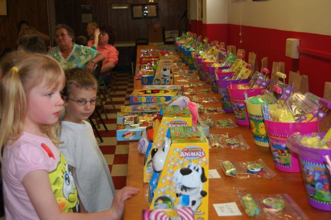 ELSA KERSCHNER/TIMES NEWS Faith Ohl and Skylar Green look at the prizes for the VFW egg hunt at Walnutport. Each child received a bucket of goodies and a game. In addition, plastic eggs had $2 in them, and there were five $5 prizes donated by Harvey…