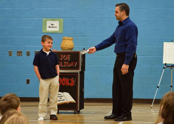 "West Penn Elementary student James Akins looks on with trepidation as magician Joe Holiday offers an undersized replacement shoe after accidently ""burning"" his original one during the act. The ""burned"" shoe magically reappeared, unscathed, at the…"
