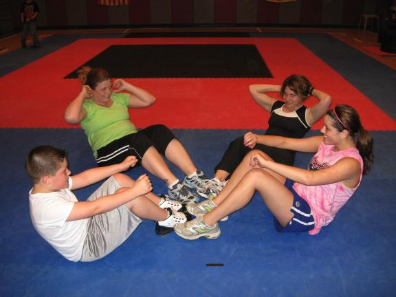 STACEY SOLT/SPECIAL TO THE TIMES NEWS TUFFCamp members Seth Paluck, 9, left, Janie Conner, Chrissy Mayernik, and Shannon Phillips, 15, do sit-ups during their weekly TUFFCamp workout, held at Mountain Karate Academy in Lehighton.