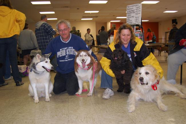Gail Maholick/TIMES NEWS Sherry White and John Haas of Lehighton live in a multi-pet household. Taking part in the Carbon County Friends of Animals rabies vaccination clinic were, from left, Misty, John Haas, Kira, Sherry White, Twizzler and Buddy.