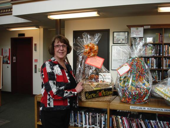 MARY TOBIA/SPECIAL TO THE TIMES NEWS Darlene Risteter, Chairman of the Ways and Means Committee shows off just a few of the fifty-four themed baskets that lucky winners took home during the annual Spring Basket Spectacular organized by The Concourse…