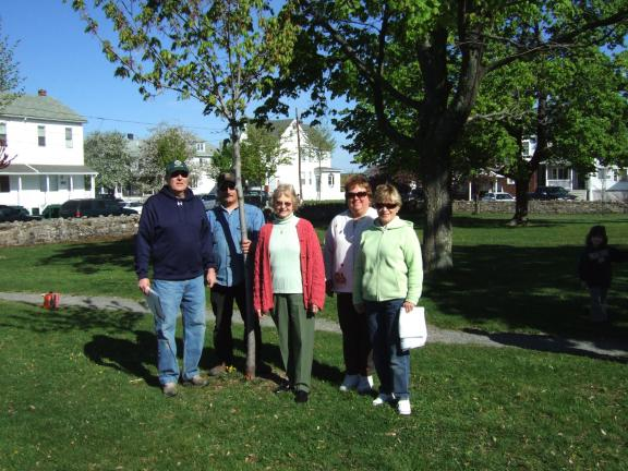 KATIE WARGO/SPECIAL TO THE TIMES NEWS Summit Hill Historical Society representative Maxine Vermillion (second from right) poses near one of three memorial trees planted in memory of prominent town clergymen by the society during this year's program…