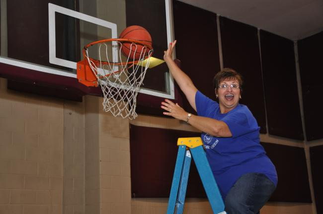 "AMY ZUBEK/TIMES NEWS Linda Swartz of the Palmerton team shows the Carbon County Senior Games participants how she ""dunks"" a basketball prior to the start of competition on Wednesday. Swartz won a bronze medal in the basketball shoot in her division."
