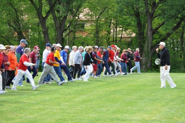 AMY ZUBEK/TIMES NEWS Senior participants from the five Carbon County Senior Centers begin the Philip Steigerwalt Memorial Walk on Tuesday morning. Victor Pituch, director of the games, right, announced the start of the event.