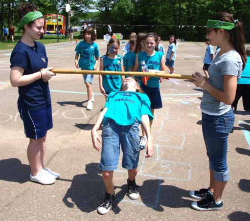 ANDREW LEIBENGUTH/SPECIAL TO THE TIMES NEWS Amy Hadesty, 10, makes it under the stick during a game of musical limbo.
