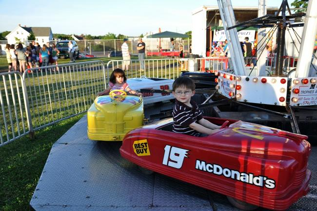 RON GOWER/TIMES NEWS The Summit Hill 500? Aiden Acevedo, 3, of Sinking Spring, Berks County, and Caroline Breslin, 1 1/2, of Summit Hill, ride in stationary cars during the Summit Hill Stay-at-Home Festival on Sunday. Great weather made it a very…