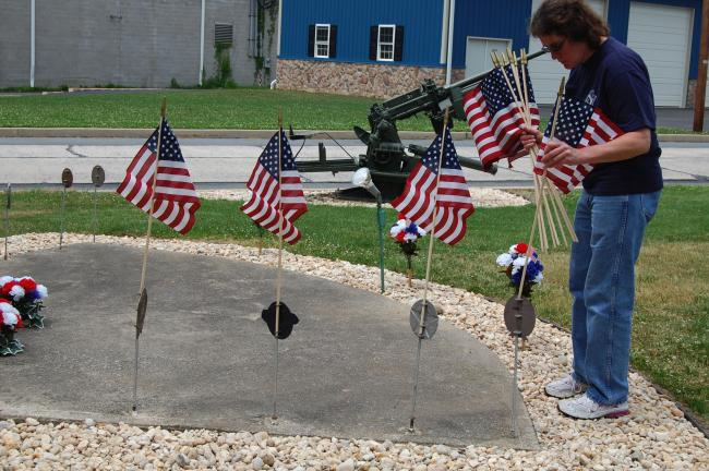 ELSA KERSCHNER/TIMES NEWS Auxiliary President Karen Bandzi puts flags in the memorial markers in front of the Walnutport Veterans Memorial.