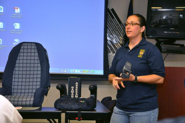 AMY ZUBEK/TIMES NEWS State Trooper Shannon Yorke of the Hazleton barracks explains about the different types of car seats available during a recent meeting of the Carbon County Child and Family Collaborative.