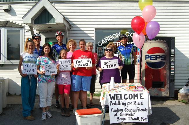 VINNY VELLA/TIMES NEWS Members of the Carbon County Friends of Animals greeted the Pedaling4Paws group with energy bars and orange juice during the riders' stop in Jim Thorpe Wednesday.