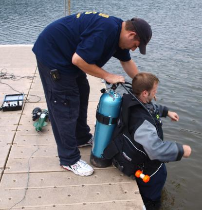 Ryan Township Dive Team and Rescue Squad Derek Davidson helps diver Michael Harris with an air tank as part of their demonstration.