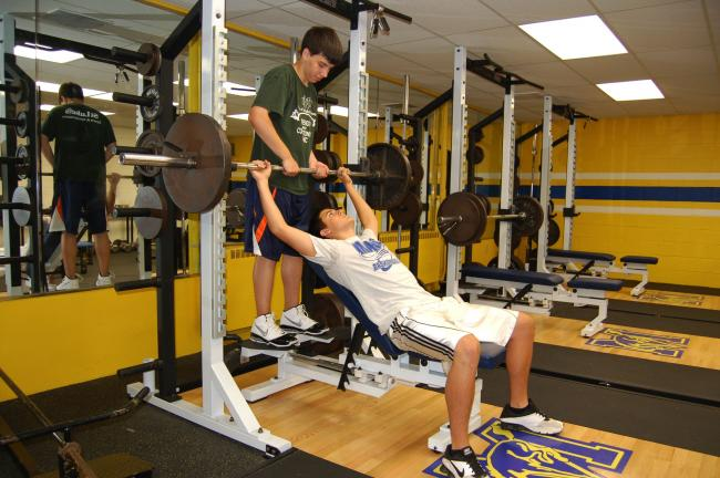 CHRIS PARKER/TIMES NEWS Marian High School students Ryan Karnish, standing, and John Julian, lifting, work out on new equipment purchased for the Dr. David J. Newton Fitness/Wellness Center at the school.