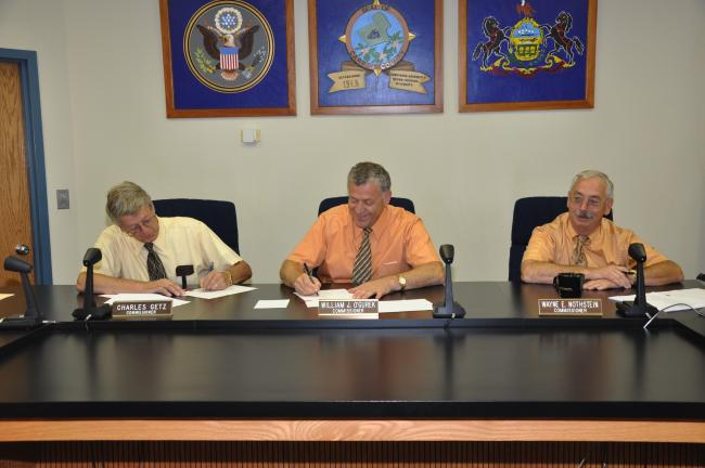 AMY ZUBEK/TIMES NEWS The board of commissioners, from left, Charles Getz, William O'Gurek, and Wayne Nothstein, signed the documents to sell Weatherwood to Guardian Elder Care of Brockway. The sale became official at midnight.