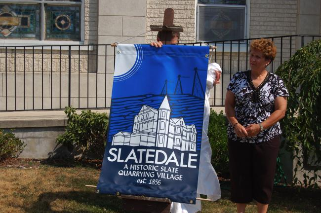 TERRY AHNER/TIMES NEWS Cynthia Snyder, postmaster and local historian, unveils a sample of the new banners that will adorn Main Street in Slatedale during a news conference Tuesday.